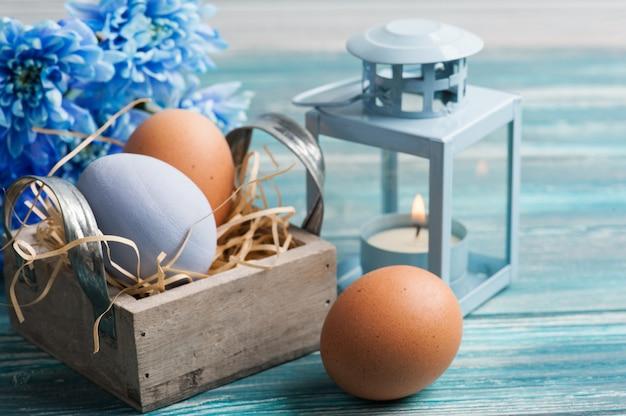 Composição de páscoa com ovos, flores azuis e velas Foto Premium