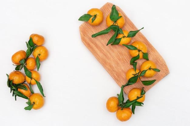 Composição de pequenas tangerinas com folhas verdes em branco Foto Premium
