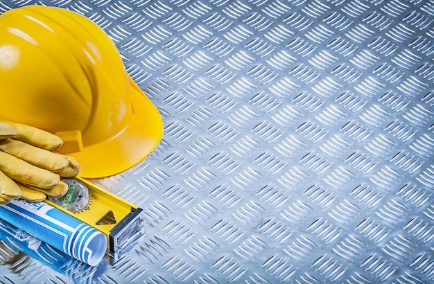 Composição de plantas laminadas azuis, construção de nível de construção de luvas de segurança de capacete em fundo de metal ranhurado Foto Premium