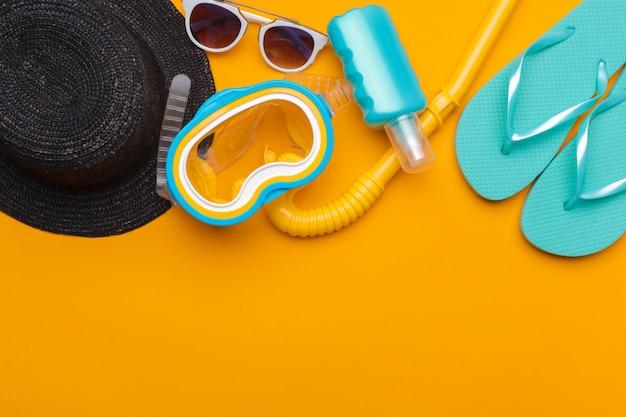 Composição de roupa de praia e acessórios em um fundo amarelo Foto Premium