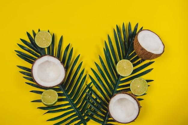 Composição de verão com cocos, limas e folhas de palmeira Foto gratuita