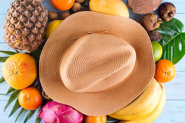 Composição de verão. folhas de palmeira tropical, chapéu, muitas frutas no fundo de madeira azul. Foto Premium