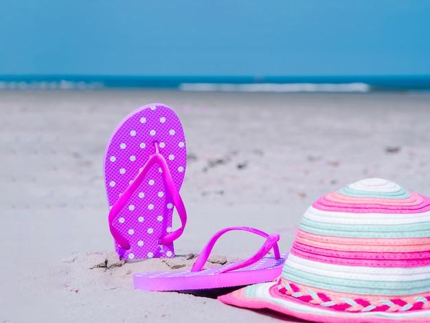 Composição de verão luz solar. chinelos de praia na areia do oceano tropical. contra o mar azul e a parede do céu. acessórios de praia conceito de férias de verão de férias na praia, passeio no mar, verão ensolarado quente Foto Premium