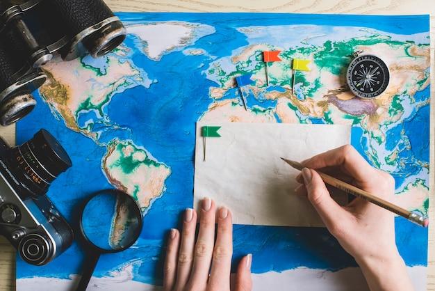 Composição de viagem com mão segurando um lápis Foto gratuita