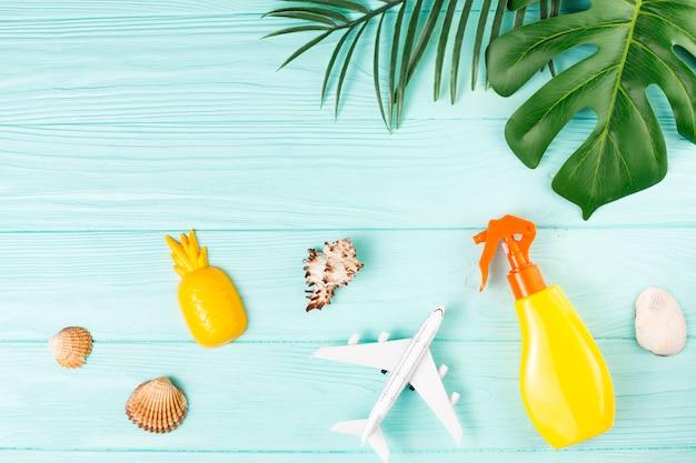 Composição de viagens exóticas com conchas, brinquedos e folhas verdes Foto gratuita
