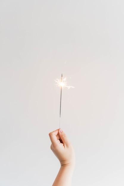 Composição do ano novo com sparkler de mão Foto gratuita