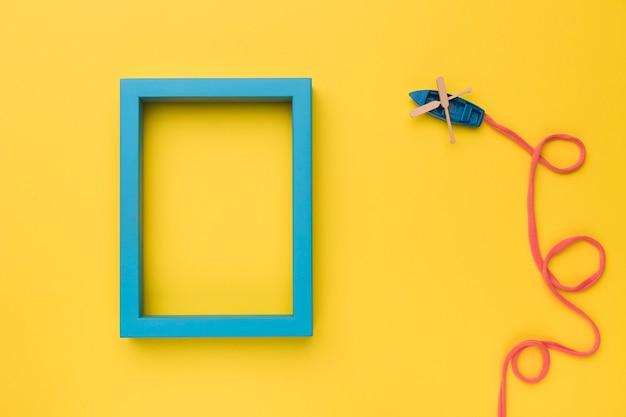 Composição do barco de brinquedo com esteira de proa e moldura azul Foto gratuita