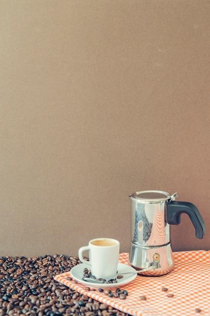 Composição do café com copo e moka em pano Foto gratuita