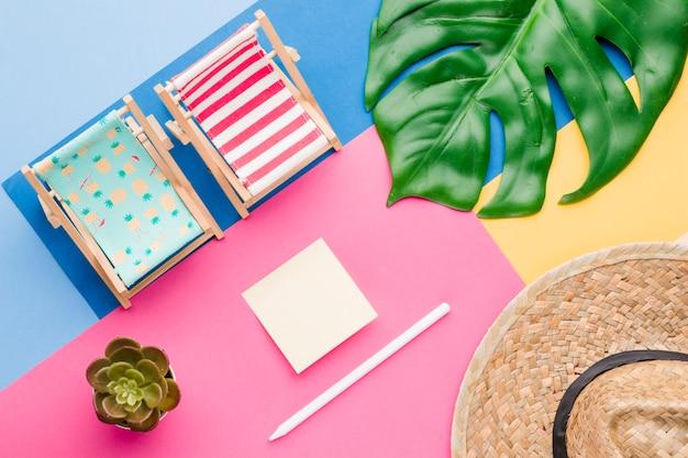 Composição do chapéu de plantas de cadeiras de convés e adesivo Foto gratuita