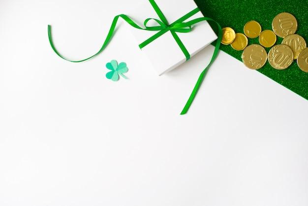 Composição do dia de são patrício. caixa de presente branca com um laço verde, um trevo de papel e moedas de ouro sobre fundo verde brilhante e branco Foto Premium