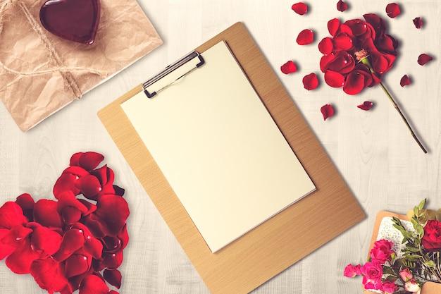 Composição do dia dos namorados com prancheta, presente e velas Foto gratuita