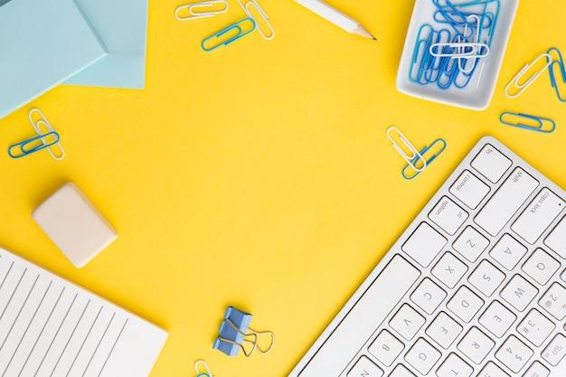 Composição do local de trabalho em fundo amarelo com espaço de cópia Foto gratuita