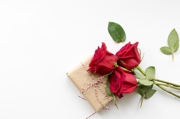 Composição do presente e buquê de rosas vermelhas em fundo branco Foto Premium