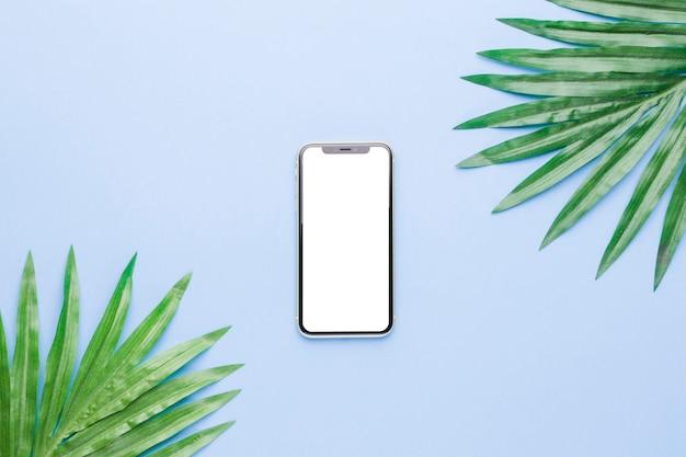Composição do smartphone com tela branca e folhas da planta Foto gratuita
