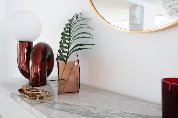 Composição elegante do candeeiro de mesa espelho vermelho com ouro estacionário em cima de mármore branco, com espaço de cópia na parede branca Foto Premium