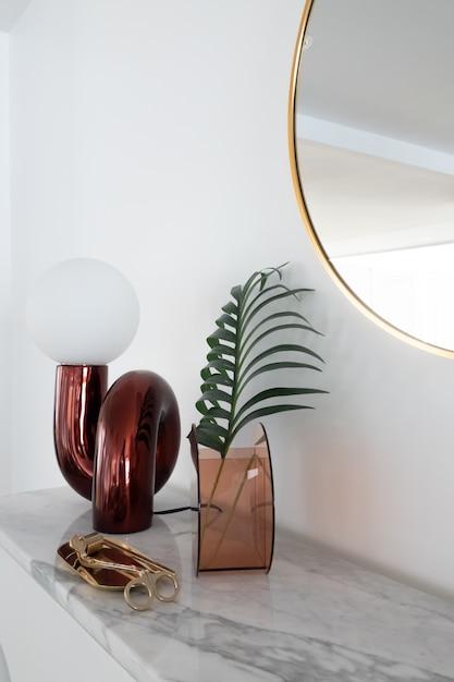 Composição elegante vista vertical do candeeiro de mesa espelho vermelho com ouro estacionário no topo de mármore branco com espaço de cópia na parede branca Foto Premium