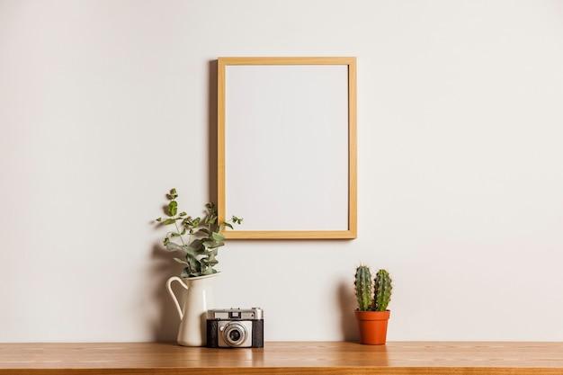 Composição floral com quadro suspenso e câmera Foto gratuita