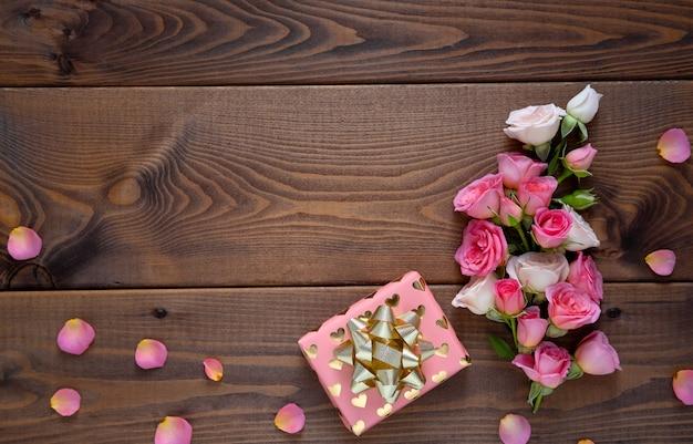 Composição floral com uma coroa de rosas cor de rosa em fundo de madeira. plano de fundo dia dos namorados. Foto Premium