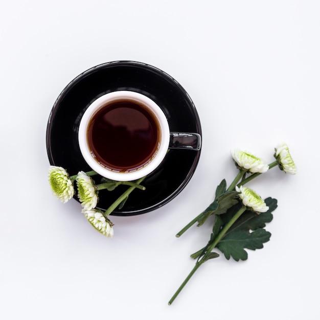 Composição floral com xícara de café preto e flores Foto gratuita