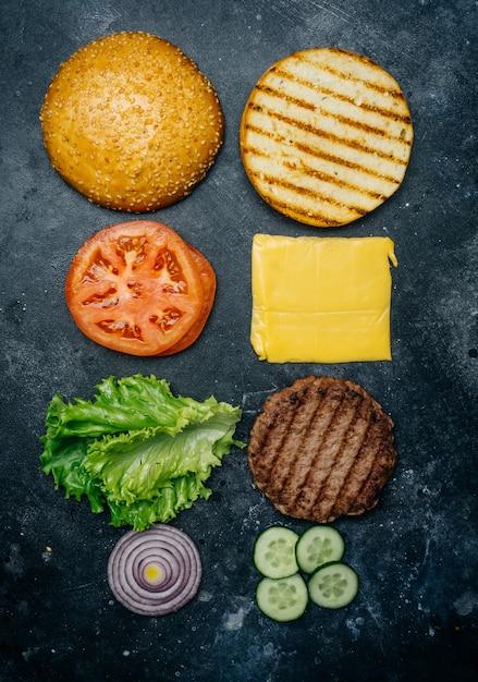 Composição home feita do hamburguer (receita). produtos para o hambúrguer clássico sobre um fundo escuro. Foto Premium