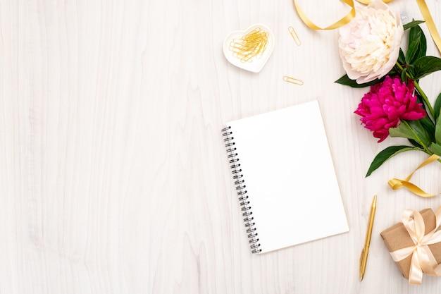 Composição mínima plana leiga com bloco de notas de papel, flores de peônia, caixa de presente e acessórios femininos. vista superior mulher mesa de escritório em casa. modelo de banner de blog de moda com espaço de cópia Foto Premium