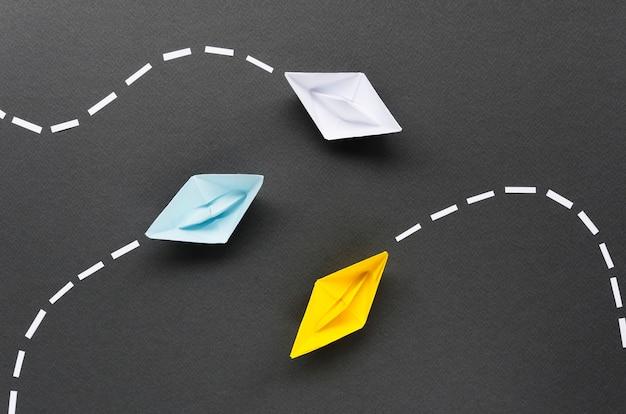 Composição para o conceito de individualidade com barquinhos de papel em fundo preto Foto Premium