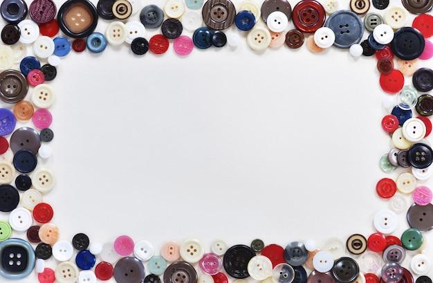Composição plana com botões e suprimentos de costura no fundo branco Foto Premium