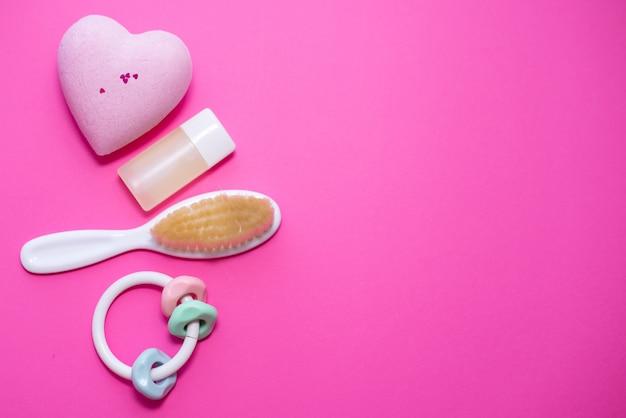 Composição plana leiga com acessórios do bebê e espaço para texto em fundo rosa Foto Premium