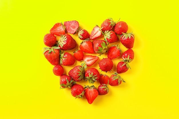 Composição plana leiga com morangos em forma de coração na cor de fundo, espaço para texto Foto Premium