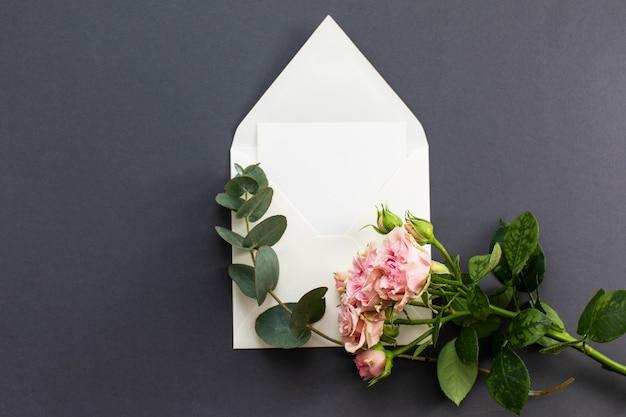 Composição plana leiga com um envelope branco, cartão em branco e uma peônia rosa flor sobre um fundo cinza. maquete para casamento ou dia dos namorados. vista do topo. Foto Premium