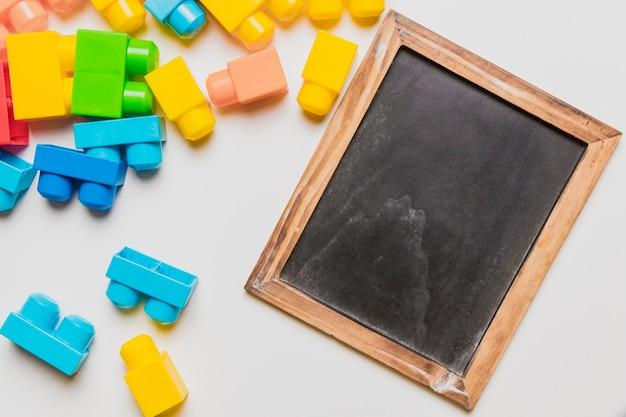 Composição plana leiga de brinquedos e modelo de ardósia Foto gratuita