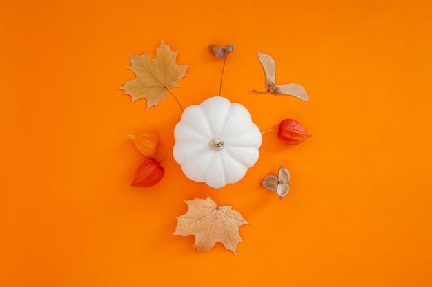Composição plana leiga de outono com abóboras brancas e folhas secas em fundo de cor laranja em negrito. outono criativo, ação de graças, outono, conceito de halloween. vista superior, copie o espaço Foto Premium