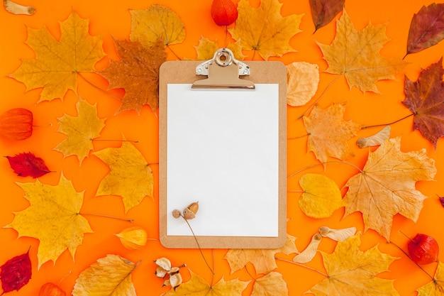 Composição plana leiga de outono com maquete de área de transferência e folhas secas em fundo de cor laranja em negrito. outono criativo, ação de graças, outono, conceito de halloween. vista superior, copie o espaço Foto Premium