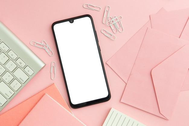 Composição plana no local de trabalho-de-rosa com telefone vazio Foto gratuita