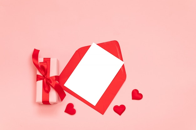Composição romântica com caixa de presente surpresa, laço de fita vermelha, envelope vermelho com papel rosa Foto Premium