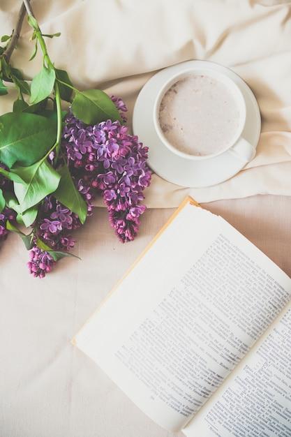 Composição romântica de manhã xícara de café com um livro e um buquê de lilases na cama Foto Premium