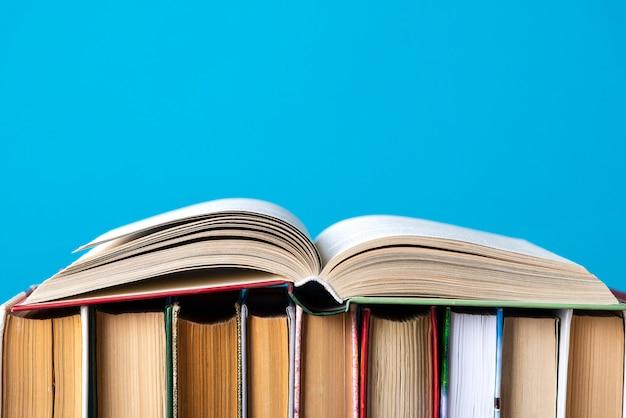 Composição simples de livros de capa dura, livros crus na mesa do deck de madeira e azul Foto Premium