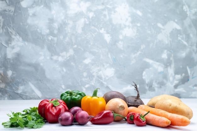 Composição vegetal com vegetais frescos, verdes, cenouras e batatas na mesa de luz Foto gratuita