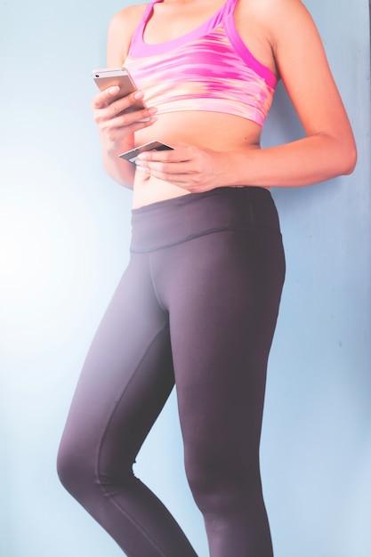 Compra online de telefonia inteligente na mão da mulher. vestuário de fitness no fundo do clube desportivo. compre itens de esporte com site de comércio eletrônico Foto gratuita