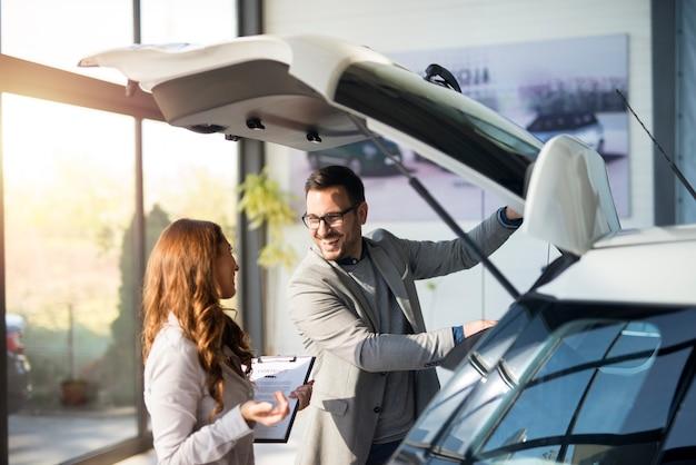 Comprador de carros testando o espaço do porta-malas de um carro novo no showroom da concessionária local Foto gratuita