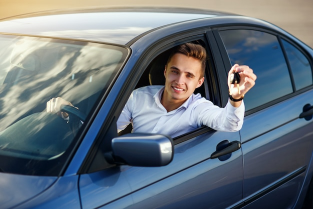 Comprador feliz segurando as chaves do carro dentro de seu novo veículo | Foto Premium