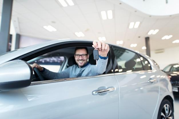 Comprador feliz sentado em um veículo novo e segurando as chaves do carro Foto gratuita