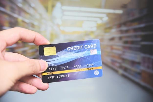 Compras com cartão de crédito no supermercado - mão segurando o pagamento com cartão de crédito Foto Premium
