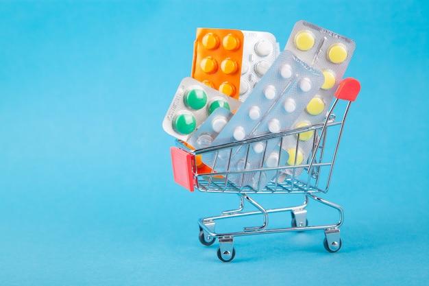 Compras de medicamentos, custos de saúde e medicamentos prescritos com um carrinho de compras cheio de pílulas Foto Premium