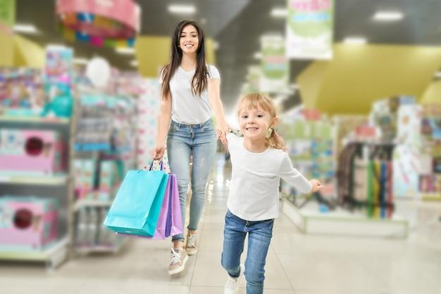 Compras em família. mãe e criança andando no shopping. Foto gratuita