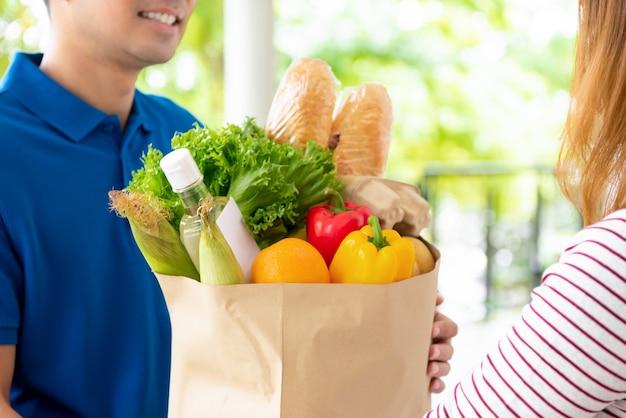 Compras entregues ao cliente em casa por um entregador, para o conceito de serviço de alimentação on-line Foto Premium