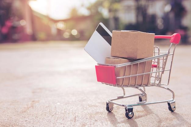 Compras on-line conceito: caixas ou caixas de papel e cartão de crédito no carrinho de compras. conectados Foto Premium