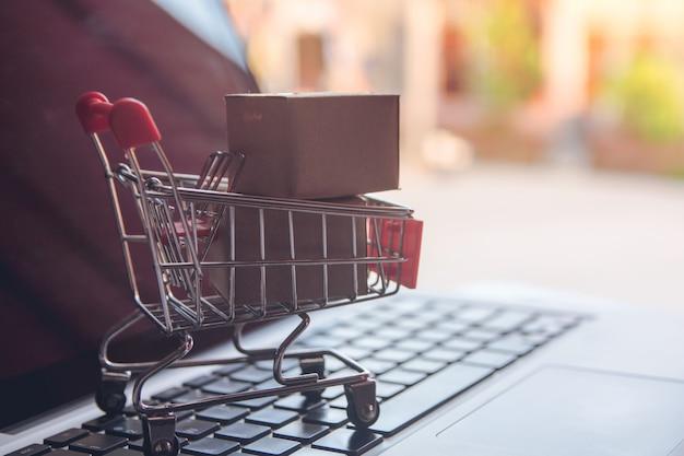 Compras on-line conceito - compras com pagamento por cartão de crédito carrinho de compras em um laptop Foto Premium