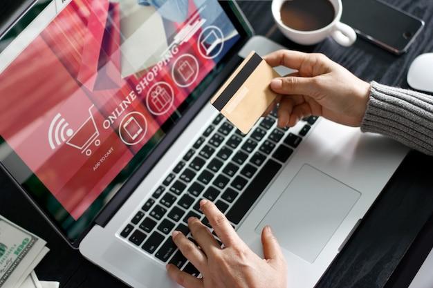 Compras on-line conceito. mulher, segurando, ouro, cartão crédito, em, mão, e, shopping online Foto Premium