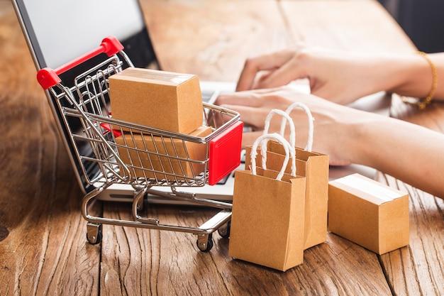 Compras on-line em casa conceito. caixas em um carrinho de compras em um teclado de laptop. Foto Premium